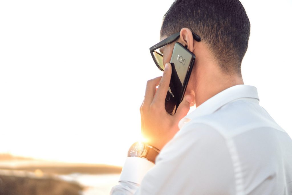 Man on the phone looking at sunset